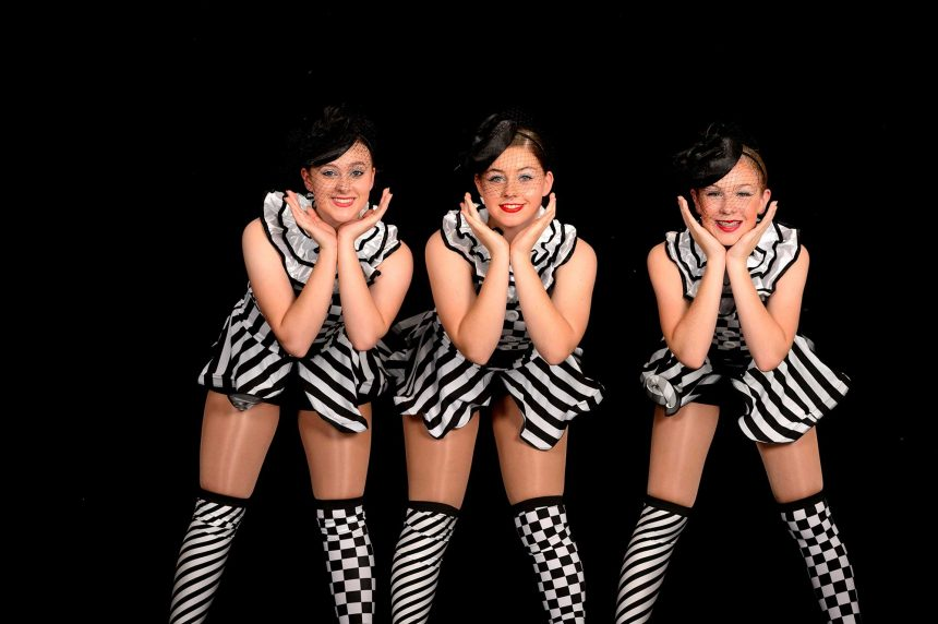 Jazz dancers in black and white clown costumes
