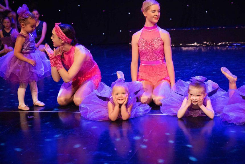 Tiny ballerinas in purple tutu costumes at concert