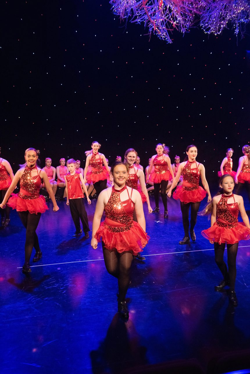 Girls and boys irish dancing in red and black costumes